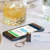 BACtrack Vio personal breathalyser on a table next to a smartphone