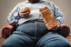 overweight man eating burger