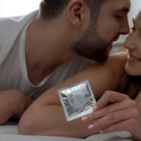 Sensible lady giving her partner a condom